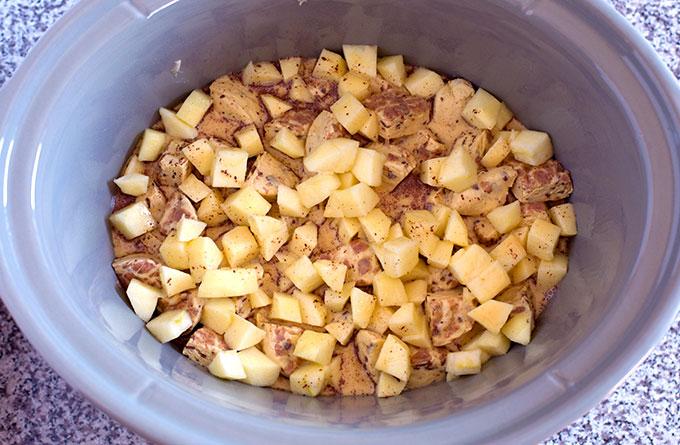 unbaked Crock Pot Apple Cinnamon Roll Casserole in a grey slow cooker