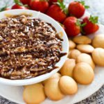 Samoas Dip in a serving bowl with fruit and cookies