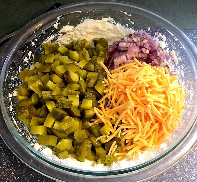 bowl of easy appetizer dip ingredients: dill pickles, cheddar cheese, red onion, cream cheese , and pickle juice