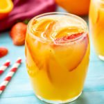 White sangria in a glass with orange slices and strawberries