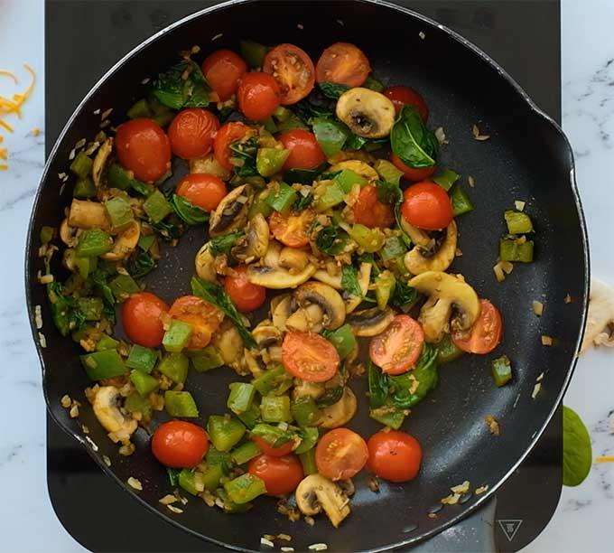 vegetables being sautéed in a skillet