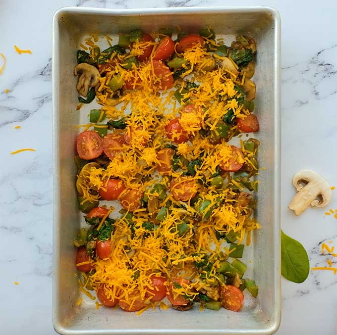 baking dish with sautéed veggies and shredded cheese