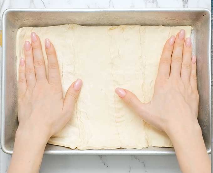 pressing uncooked crescent roll dough into a baking dish