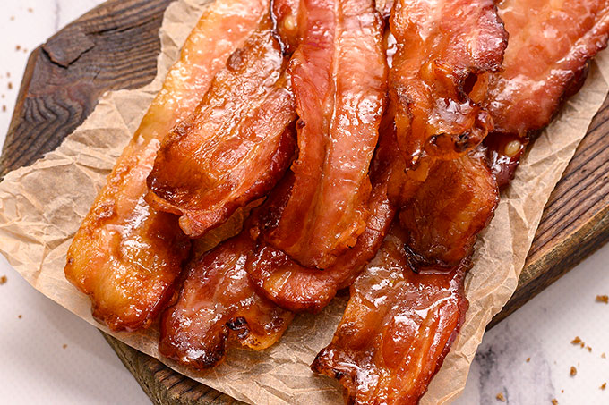 Pile of brown sugar baked bacon on a cutting board