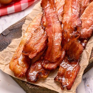 Baked Brown Sugar Bacon in a pile on a cutting board