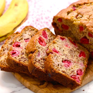 sliced raspberry banana bread on a cutting board