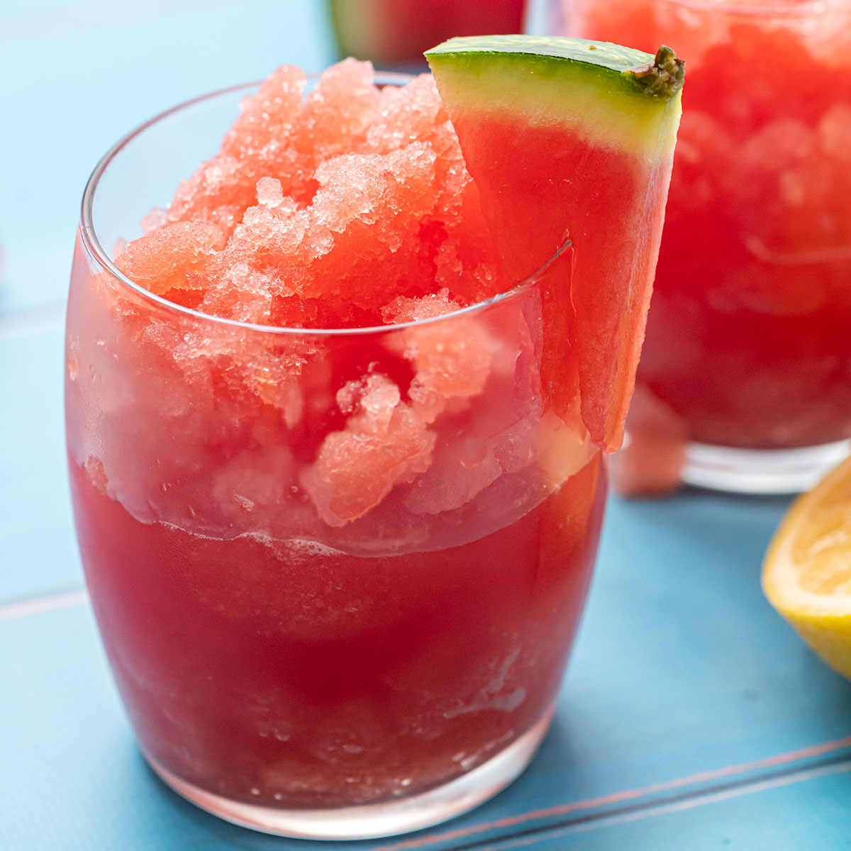 Glass full of watermelon slushy with a wedge of watermelon on the rim