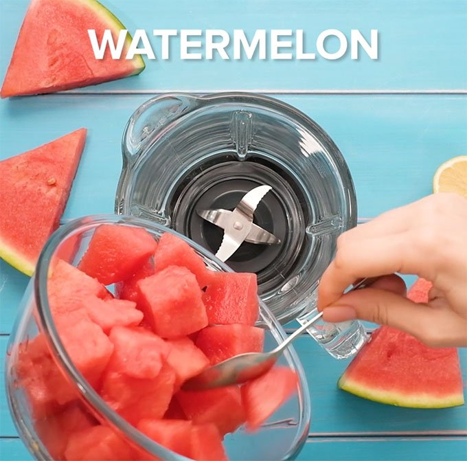 pouring chunks of watermelon into a blender
