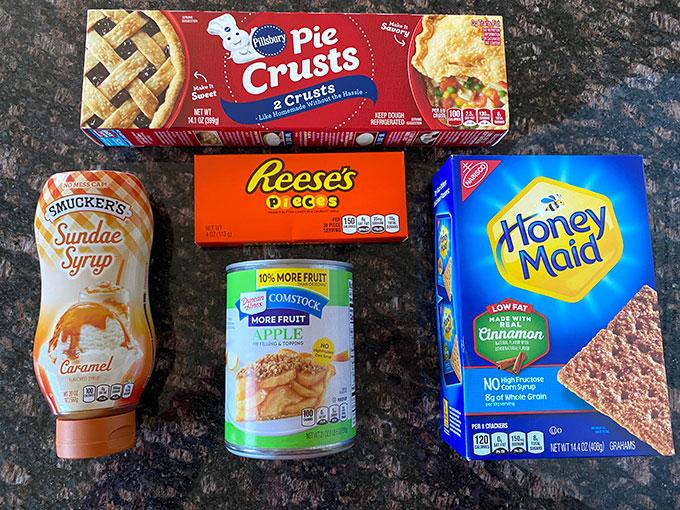 Ingredients for apple pie hack recipe:  pie crust, apple pie filling, Reeses pieces, caramel sauce, and cinnamon graham crackers