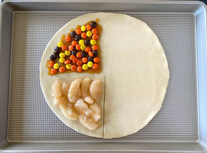 pie crust with apple pie filling, caramel, and reeses pieces on half of it.