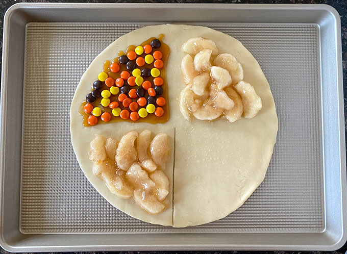 Pie crust with sections of apple pie filling and Reeses pieces