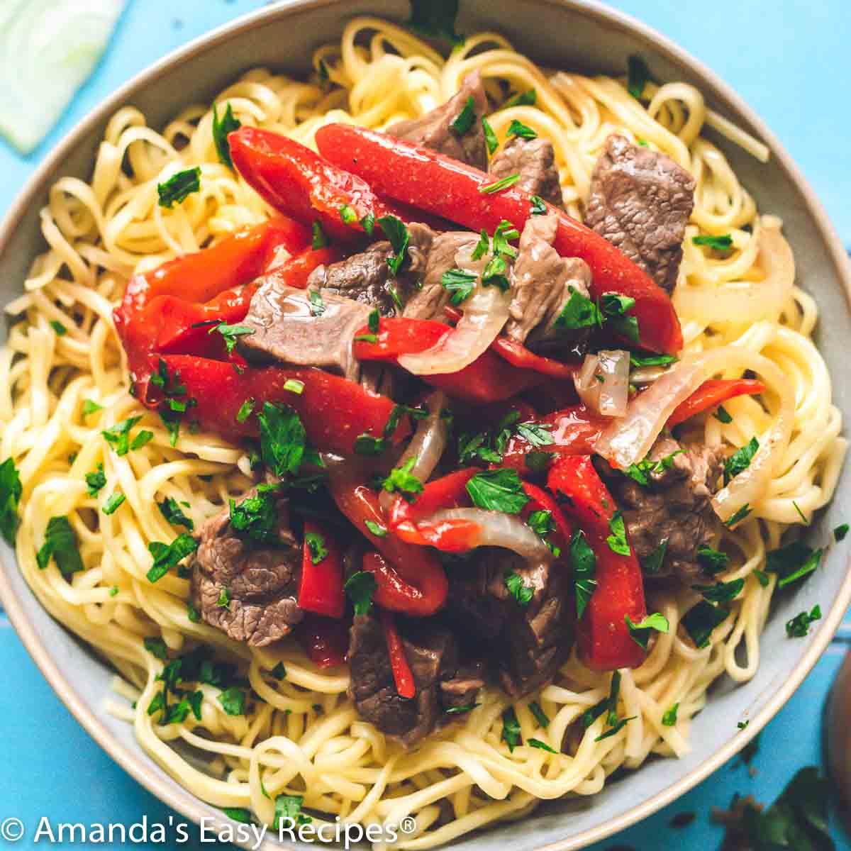 large bowl of pepper steak over cooked noodles